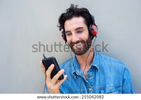 Close up portrait of a happy man smiling with mobile phone and headphones  - stock photo