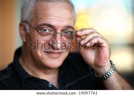 Close-up portrait of a happy mature man. Shallow DOF, focus on glasses.