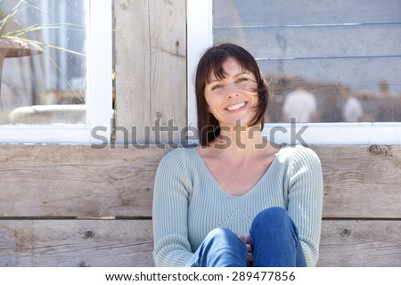 Close up portrait of a happy middle aged woman smiling outdoors - stock photo