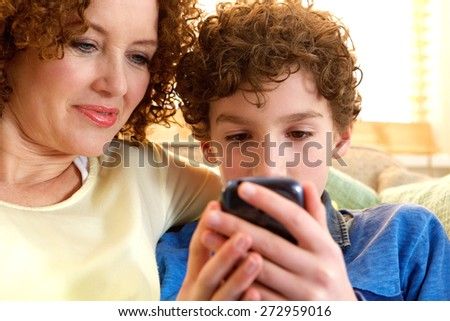 Close up portrait of a happy mother and son looking at mobile device - stock photo