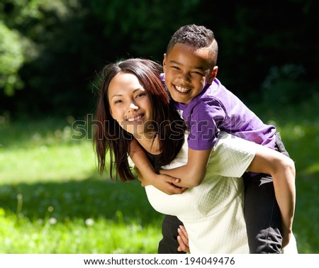 Close up portrait of a happy mother and son smiling together outdoors - stock photo