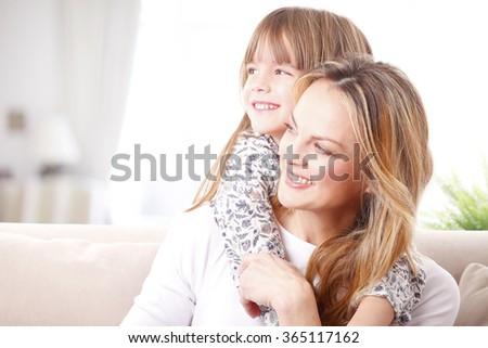 Close-up portrait of a happy mother hugging her adorable daughter while sitting on sofa at home.  - stock photo