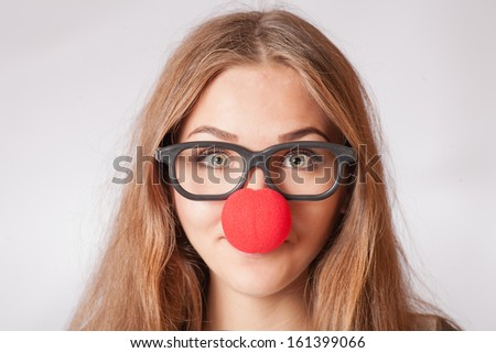 Close-up portrait of a happy 20s girl with red clown nose. Funny portrait of young woman in party glasses - stock photo