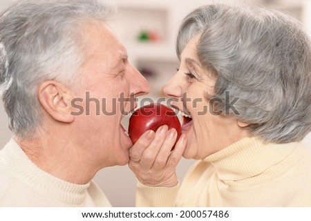 Close-up portrait of a happy senior couple eating apple at home - stock photo