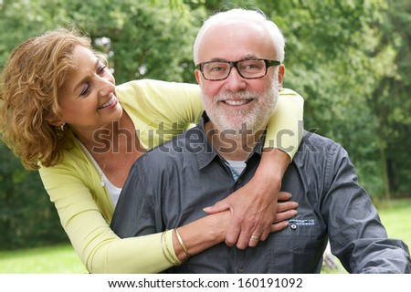 Close up portrait of a happy senior man and beautiful older woman smiling together - stock photo