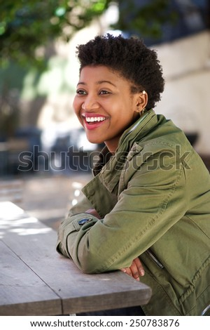Close up portrait of a happy young african american woman sitting outside