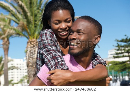 Close up portrait of a happy young couple laughing together outdoors - stock photo