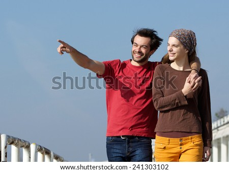 Close up portrait of a happy young couple walking outdoors and pointing  - stock photo