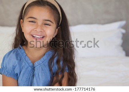 Close-up portrait of a happy young girl sitting on bed at home