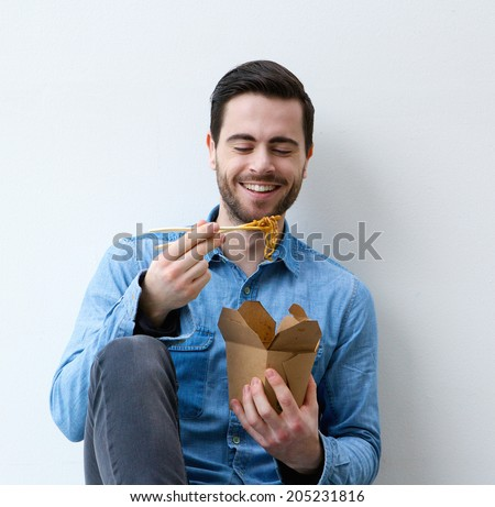Close up portrait of a happy young man eating asian food with chopsticks - stock photo