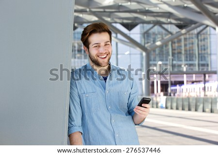 Close up portrait of a happy young man holding mobile phone - stock photo