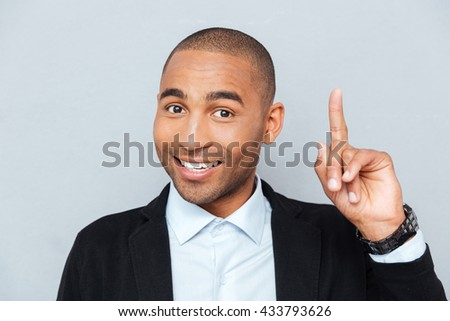 Close-up portrait of a happy young man pointing finger up at something interesting isolated on gray background - stock photo
