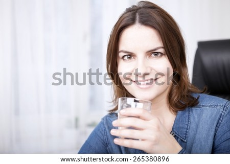 Close up Portrait of a Happy Young Woman in Denim Outfit Holding a Glass of Water While Looking at the Camera. - stock photo