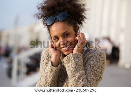 Close up portrait of a happy young woman listening to music on headphones outdoors - stock photo