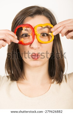 Close up portrait of a happy young woman looking through red and yellow bell pepper slices pretending to be glasses, studio shot on white. Healthy food concept.
