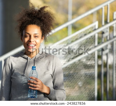 Close up portrait of a happy young woman smiling with water bottle - stock photo