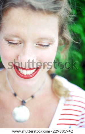 Close-up portrait of a happy young woman wearing red lipstick and natural eye makeup is laughing with her eyes closed. - stock photo