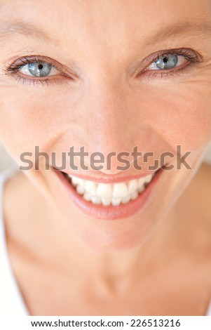 Close up portrait of a joyful healthy woman with fresh skin smiling at the camera feeling confident. Wellness and well being care and aging wrinkles with a cheerful expression, indoors.