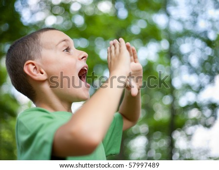 Close up portrait of a kid yelling into the forest - stock photo