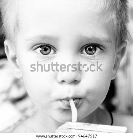 close-up portrait of a little boy drinking with straw. Black and white photo - stock photo