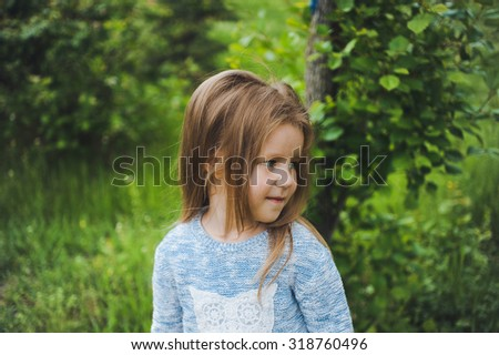 close-up portrait of a little girl child with blond hair in a park wearing a sweater with owl posing and smiling - stock photo