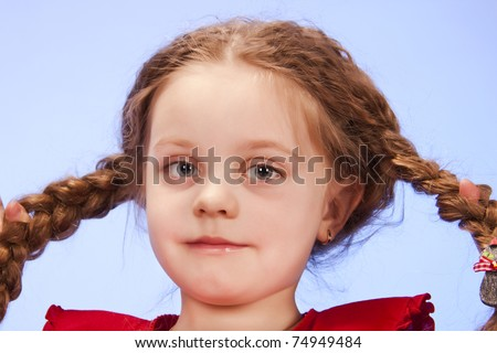 Close up portrait of a little girl with pigtails on a blue background