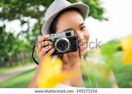 Close-up portrait of a lovely young photographer taking a picture of you - stock photo
