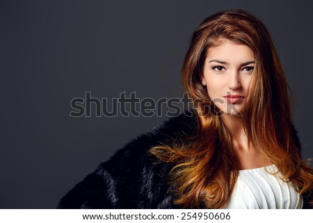 Close-up portrait of a magnificent young woman wearing fur jacket. Studio shot. Beauty, fashion. Make-up, cosmetics. Copy space. - stock photo