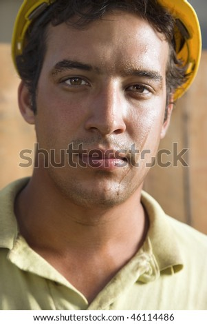 Close up portrait of a male Caucasian construction with a dirty face. He is looking directly into the camera. Vertical shot. - stock photo