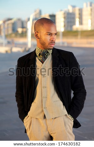 Close up portrait of a male fashion model posing outdoors with trendy jacket - stock photo