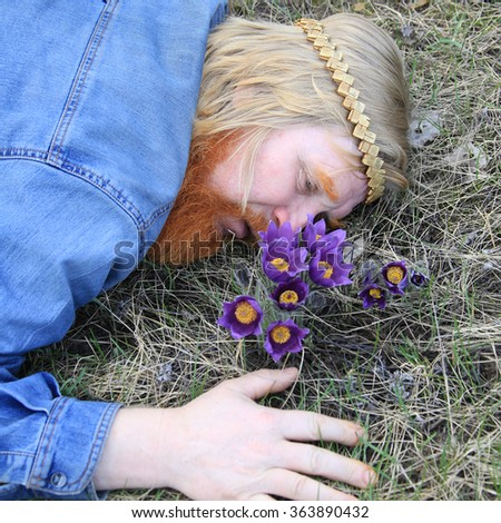 close-up portrait of a man with a red beard and a mustache, lying in a meadow with snowdrops in spring day - stock photo