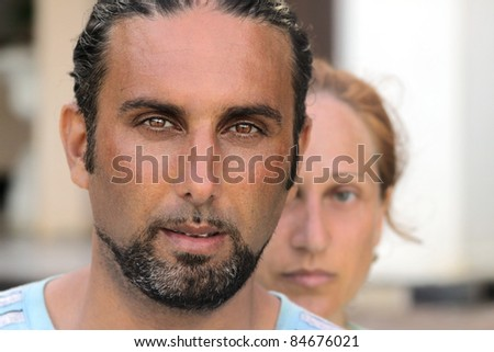 Close up portrait of a man with a woman behind him
