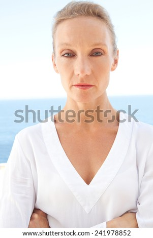 Close up portrait of a mature beautiful caucasian woman standing against a blue sea and sky with a determined and stubborn strong thoughtful expression. Healthy lifestyle, wellness and care outdoors. - stock photo