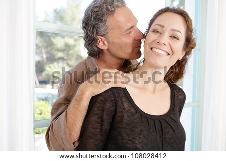 Close up portrait of a mature couple being playful and kissing at home - stock photo