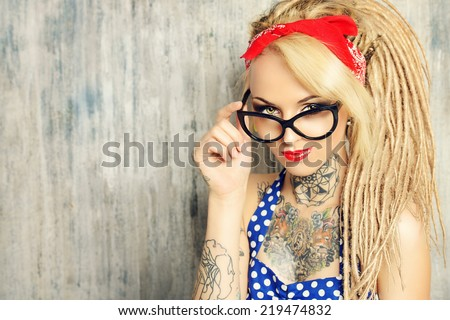 Close-up portrait of a modern pin-up girl wearing old-fashioned polka-dot dress and spectacles and modern dreadlocks. Fashion shot.  - stock photo
