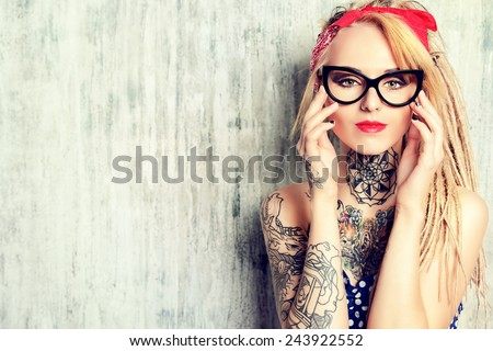 Close-up portrait of a modern pin-up girl wearing old-fashioned polka-dot dress and spectacles and modern dreadlocks. Fashion shot. Tattoo. - stock photo