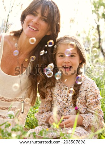 Close up portrait of a mother and daughter relaxing on holiday, holding their heads together joyfully smiling looking at floating bubbles in a green field. Family activities lifestyle, outdoors. - stock photo