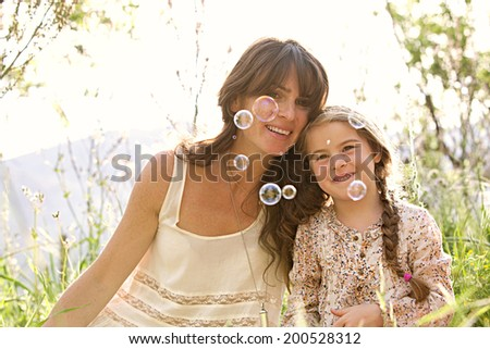 Close up portrait of a mother and daughter relaxing on holiday, with their heads together, smiling with fun expressions looking at floating bubbles in a green field. Family activities lifestyle. - stock photo