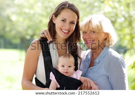 Close up portrait of a mother and grandmother smiling with baby - stock photo
