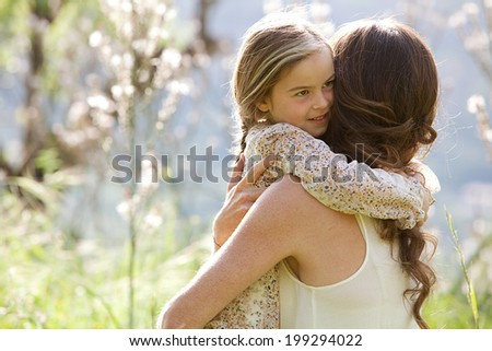 Close up portrait of a mother and young daughter relaxing together in a beautiful green spring field of flowers hugging and enjoying a sunny holiday outdoors. Family love holiday activities lifestyle. - stock photo