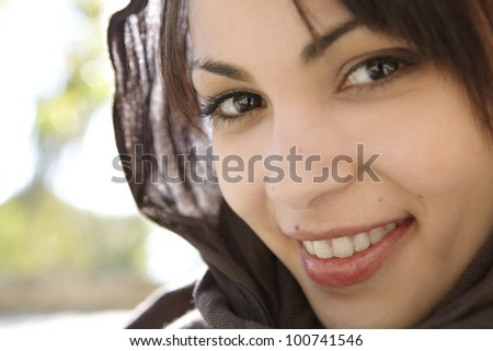 Close up portrait of a muslim woman wearing a head scarf smiling at camera. - stock photo