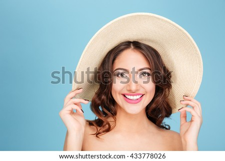 Close-up portrait of a pretty beautiful brunette wearing beach hat and swimsuit isolated on the blue background - stock photo