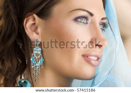 close up portrait of a pretty brunette with blue-sky earring playing to hide her face with a summer headscarf