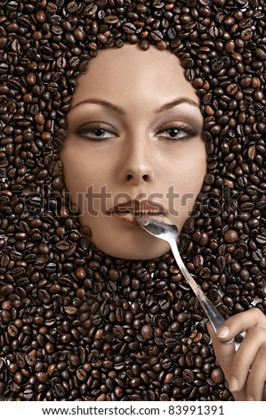 close up portrait of a pretty girl immersed in coffee beans with a spoon in her mouth - stock photo
