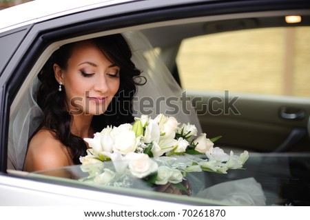 close-up portrait of a pretty shy bride in a car window - stock photo