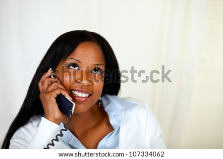 Close up portrait of a pretty woman smiling and conversing on phone - stock photo