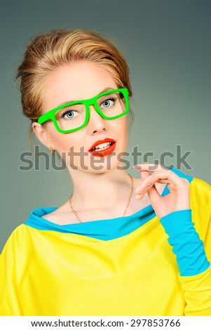 Close-up portrait of a pretty young womanl posing in vivid colourful clothes and glasses. Bright fashion. Optics, eyewear. Studio shot.