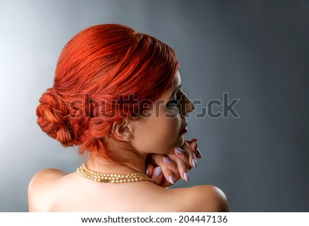 Close up portrait of a redhead woman with elegant braided hairstyle isolated over gray - stock photo