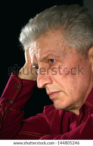 close-up portrait of a sad old man on a black background