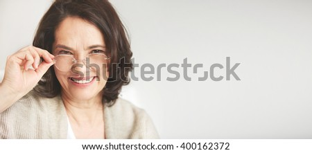 Close up portrait of a senior Attractive middle-aged brunette woman with a beautiful smile relaxing at home with copy space for your text message or promotional content - stock photo
